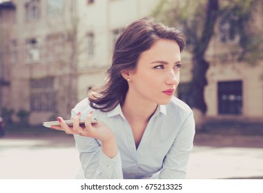 Frustrated woman waiting for a phone call or message from her boyfriend sitting outside in the street with an urban background
