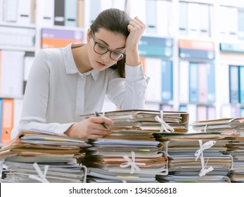 Frustrated you office worker leaning on piles of paperwork, she is overloaded with work and stressed