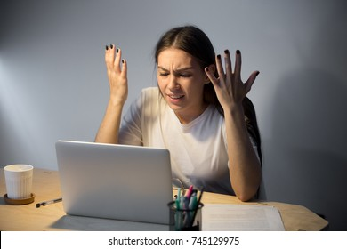 Frustrated young adult woman looking in laptop computer late at night, fling arms up.  She just found mistake in last assignment error in contract disagreement in email or dissatisfied buyer message.