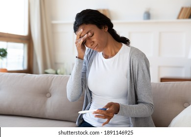 Frustrated young african american woman looking at pregnancy test, feeling stressed of unwanted results. Unhappy millennial multiracial lady holding ovulation stick, upset with infertility at home.