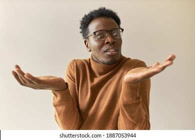 Frustrated young African man in trendy glasses shrugging shoulders in bewilderment, having confused doubtful look, spreading palms, feeling uncertain about making decision, weighing all pros and cons