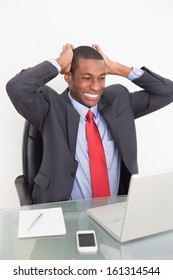 Frustrated young Afro businessman looking at laptop at desk against white background