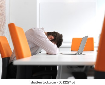 Frustrated young business man have stress problems. Sitting alone at office meeting room  and working on laptop compute.