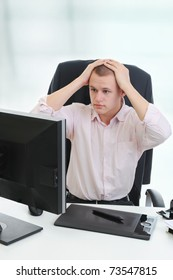 Frustrated young businessman in front of computer.