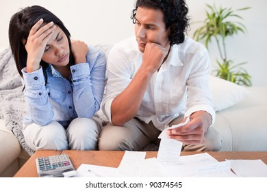 Frustrated young couple checking their bills