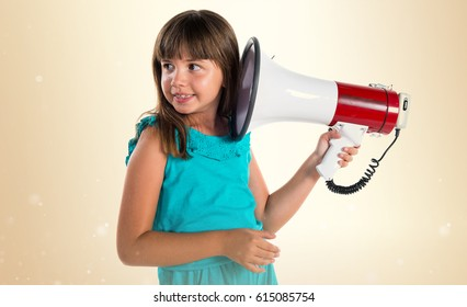 Frustrated young girl shouting by megaphone