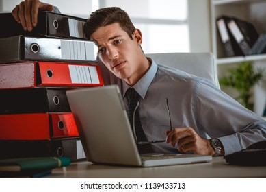 Frustrated young handsome man looking exhausted and leaning at the binders, while sitting at his working place