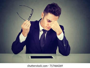 Frustrated young handsome man looking exhausted feeling tired sitting at his working place and carrying his glasses in hand