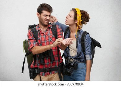 Frustrated young male dressed in checkered shirt scratching his wrist and female slapping him on cheek while being attacked by Mosquitos during hiking trip in mountains. Horizontal studio portrait