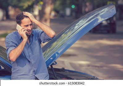 Frustrated young man calling roadside assistance after breaking down. Long waiting time concept