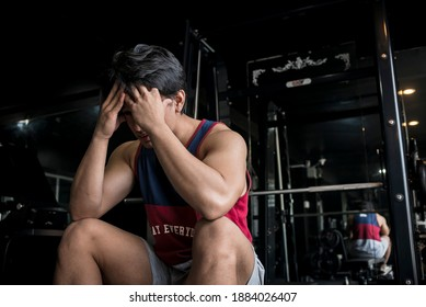 A frustrated young man holds his hands up to his forehead. Concept of workout plateau at the gym.