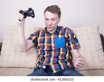 Frustrated young man playing  video games sitting at sofa and holding remote controller