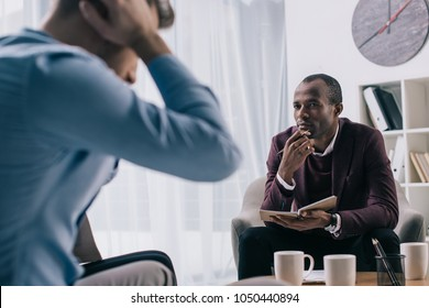 Frustrated young man sititng on sofa and african american psychiatrist in office