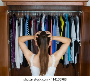 Frustrated young woman cannot decide what to wear from her closet