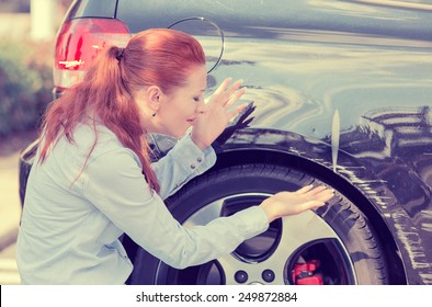 Frustrated young woman checking pointing at car scratches and dents outdoors outside