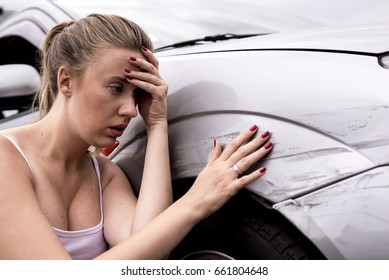 Frustrated young woman checking pointing at car scratches and dents outdoors during the day,  car crash accident,  accident insurance. Stressed Driver Sitting At Roadside.Young woman is terrified