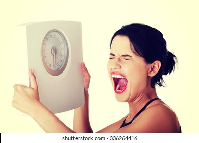 Frustrated young woman with scale.