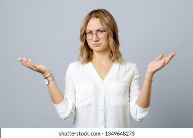 Frustrated young woman shrugs shoulders with her arms out isolated on gray background