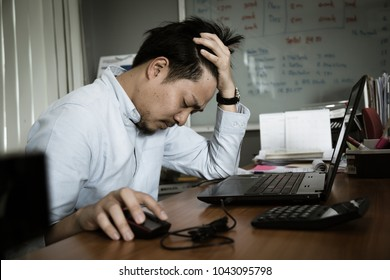 Frustrated young working man feeling stressed , sick , tired  or depress working on laptop at business office