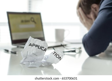 Frustration in job search. Unemployed man cant' find work. Jobless, sad, confused, worried and tired person holding hands on face. Ripped application paper on home office table. Employment concept.