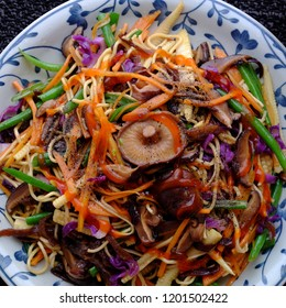 Fry noodles mixed vegetables, a Vietnamese vegetarian dish for vegans, with colorful greens, vermicelli and mushrooms, quick to  make for breakfast at home