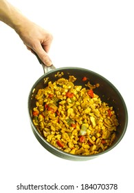 Fry pan with chicken with curry, red pepper and corn held by a male chef towards white background