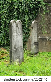 FRYDEK-MISTEK, CZECH REPUBLIC – July 2: beautiful old tombstones and the wall covered with ivy on the jewish cemetery in Frydek-Mistek, Czech Republic, July 2, 2017