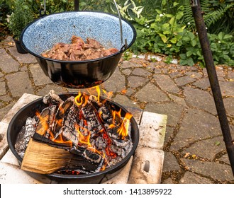 Frying the beef in a cauldron over an open wood fire to prepare the Hungarian cauldron goulash.