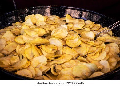 frying chips in a black pan with a lot of boiling oil in a restaurant