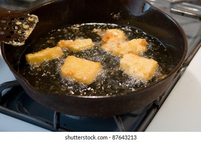 Frying corn meal mush in hot oil in an iron pan - a traditional country and soul food dish in the U.S., Latin America, and elsewhere
