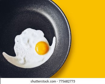 Frying egg in a non stick frying pan on a yellow background, close up top view with copy space
