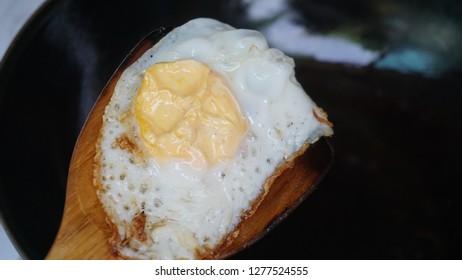 Frying egg on pan.