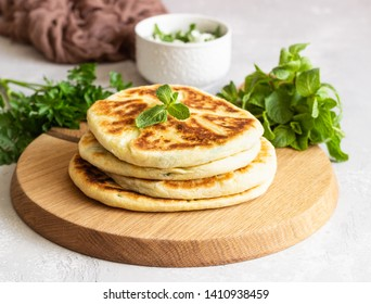 Frying flatbread filled with fresh herbs and cheese. Khychiny or qutab - traditional caucasian or Azerbaijani flatbread.