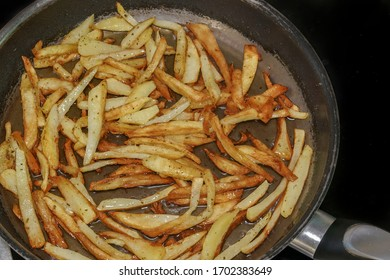 Frying French fries in hot olive oil at home kitchen close up. Top view of preparing fresh cut house made fried potatoes on a cooking pan with boiling oil.