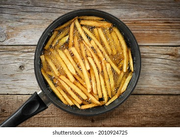 Frying French fries in a pan with oil, top view