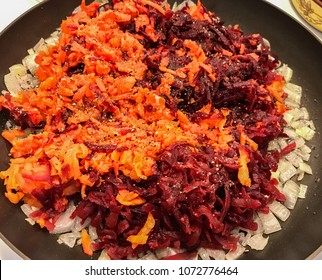 Frying fresh onion, carrot and beetroot on the stove in frying pan, closeup