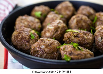 Frying large homemade Italian meatballs on a midium frying pan for dinner.