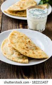 Frying pan baked flat bread on a plate with glass of sour milk. Yantyk - traditional Crimean tatar flatbread