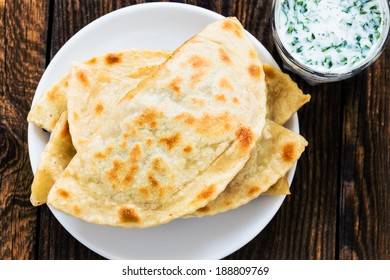 Frying pan baked flat bread on a plate with glass of sour milk. Yantyk - traditional Crimean tatar flatbread viewed from above