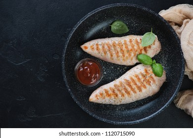 Frying pan with barbecued turkey breast fillet, flatlay on a black stone background, horizontal shot with copyspace