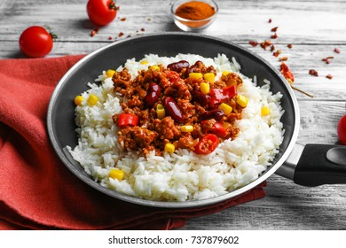 Frying pan with chili con carne and rice on table