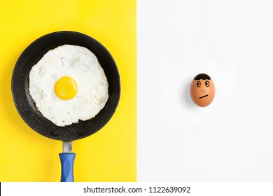 Frying pan with cooked egg and raw egg drawn face looking worried.