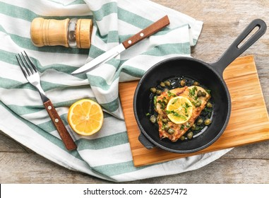 Frying pan with delicious chicken piccata on wooden board
