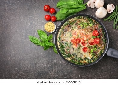 Frying pan with delicious spinach frittata on dark background