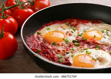 Frying pan with eggs in purgatory on wooden background