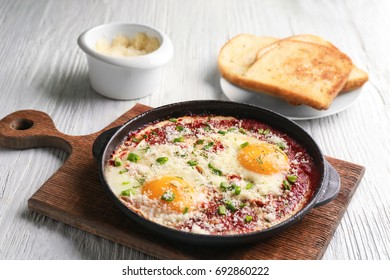 Frying pan with eggs in purgatory on wooden board