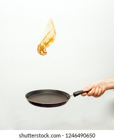 Frying pan with flying pancake isolated on white background
