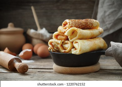 Frying pan of freshly baked pancakes,  Ingredients and kitchenware for pancakes making.
