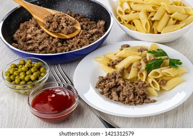 Frying pan with fried chicken mince, bowl with pasta, bowls with green peas, ketchup, white plate with macaroni, fried mincemeat, fork on wooden table