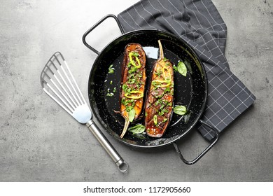 Frying pan with fried eggplant slices on table, top view